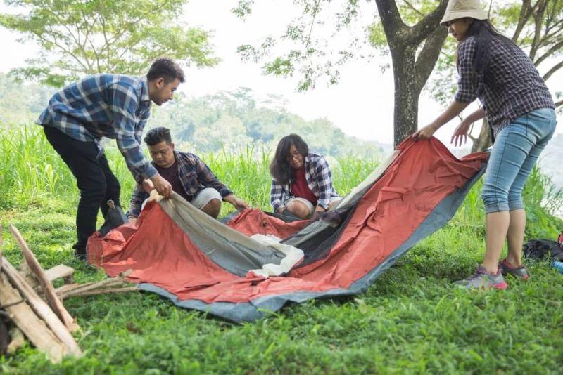 4 người đang trải lều lên trên tấm bạt